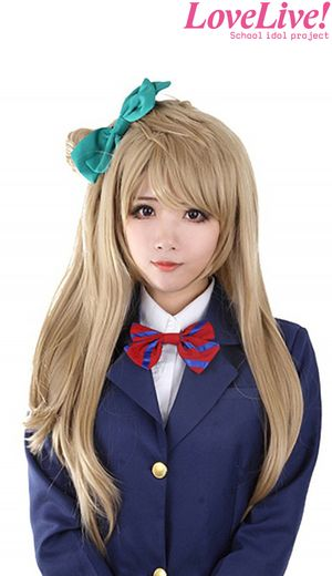 A long wavy strawberry blonde wig with a detachable tail and a clip on straight bow hair piece styled on Minami from Love Live. It measures 68cm long.  The wig is made from synthetic fibres and can be cut as desired.:
