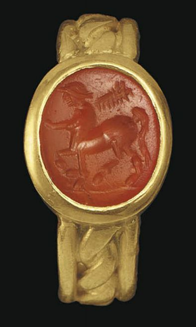 A ROMAN CARNELIAN RINGSTONE   CIRCA 1ST-2ND CENTURY A.D.   The flat oval stone engraved with a centaur striding to the left, holding a branch over his shoulders, on a groundline; mounted as a ring in a modern gold setting  7/16 in. (1.1 cm.) long; ring size 6¾: