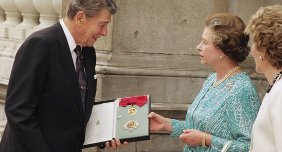 Reagan looks at the insignia of the honorary Knight Grand Cross of the Most Honourable Order of the Bath, which Queen Elizabeth II conferred on him after a lunch in Buckingham Palace on June 14, 1989.