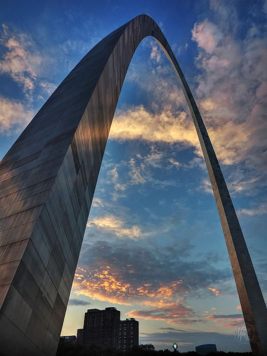 The pink hues of the clouds at sunset reflect off of the stainless steel skin of the Gateway Arch in St. Louis, MO.