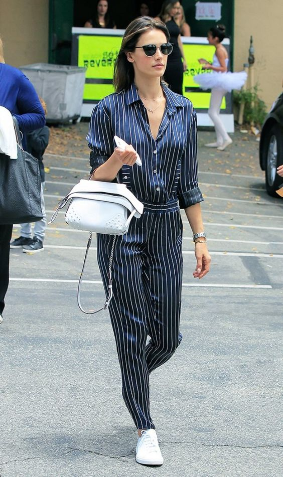 Alessandra Ambrosio makes silk pajamas work for the day time by pairing a silk pin striped jumpsuit with sneakers and a Tod's bag: