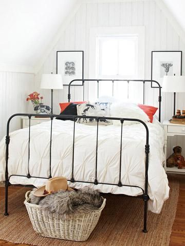 Attic bedroom - black paint updates an old iron bed; white painted bead board; framed art on either side