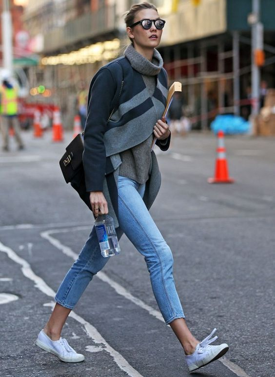 Karlie Kloss wears a gray sweater, striped jacket, cropped jeans, and sneakers.: