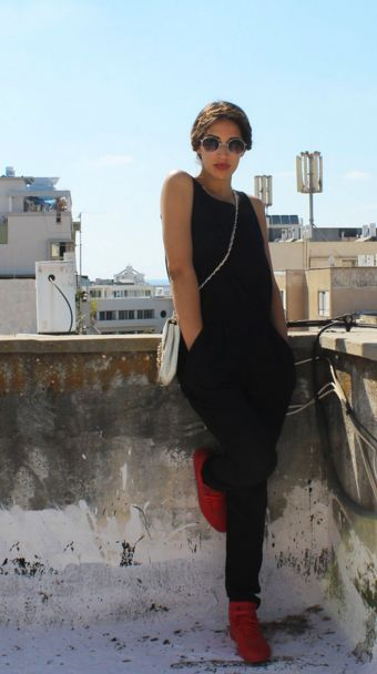 Karen Or, Israeli fashion blogger from Street Chic Tel Aviv, wears a black jumpsuit and red reebok sneakers