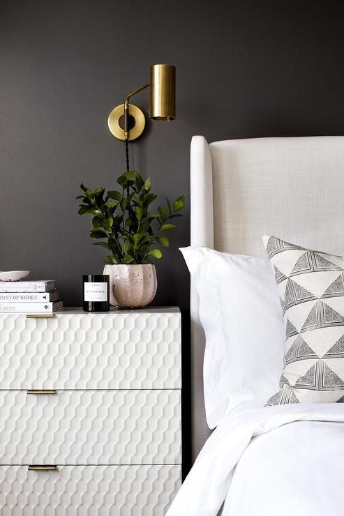 Black Bedroom Walls Contrast White Nightstand Illuminated By Brass Sconces Mounted Beside A White Wing Wall Sconces Bedroom Black Walls Bedroom Sconces Bedroom