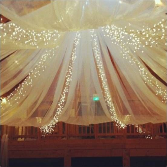 Using fairy lights and classic white draping is an effective way to make an impact.
