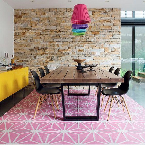 Tudo tem cor na sala de jantar: do tapete rosa aos pendentes, passando pelo aparador amarelo. O piso de concreto usinado com resina é mais neutro e fácil de limpar, ótimo para uma casa com crianças. Projeto da arquiteta Monica Drucker