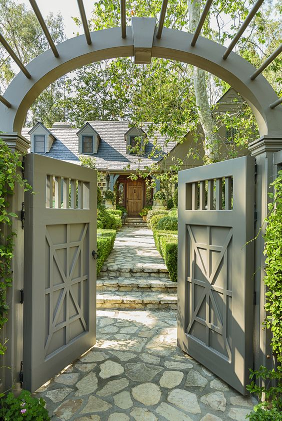 This arch-topped entry gate offers some privacy from the street and frames the approach to the house, which is paved with local flagstone.