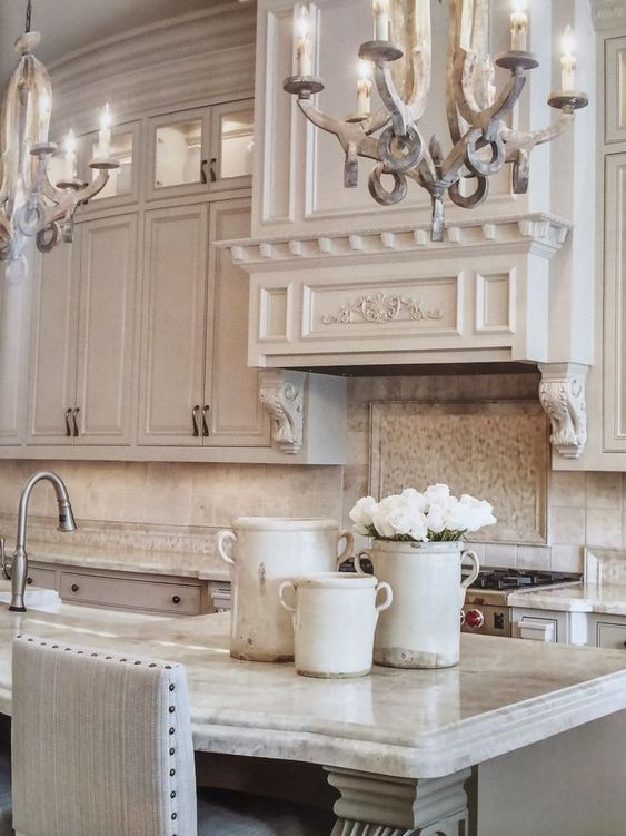 Serene kitchen decor in a French Country kitchen with romantic chandeliers, French pots, and magnificent cabinetry. #frenchcountry #kitchendecor #kitchendesign #chandeliers #whitekitchen #serene #timeless #oldworld #luxurykitchen #greykitchen