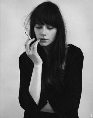 ロングヘアのクールな女性がタバコを吸う画像