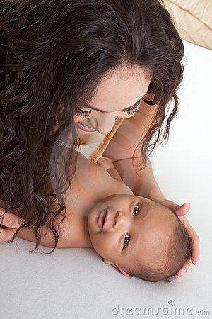 image photo : Latina mother playing with her baby boy son on bed
