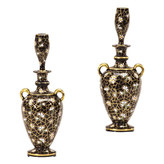 Pair of Bohemian Black Crystal Perfumes with Enamel Decoration  Bohemia, Czechoslovakia  ca. 1880's  Wonderful pair of hand blown, black crystal perfume bottles with matching stoppers.The entire body is hand painted with raised enamel flowers and highlighted in gold. The stoppers are shaped like small vases as they were probably also used as perfumes to scent the air. The handles add another decorative element.