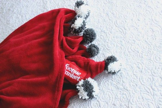 Make a plain blanket suMake a plain blanket super cute with pompoms