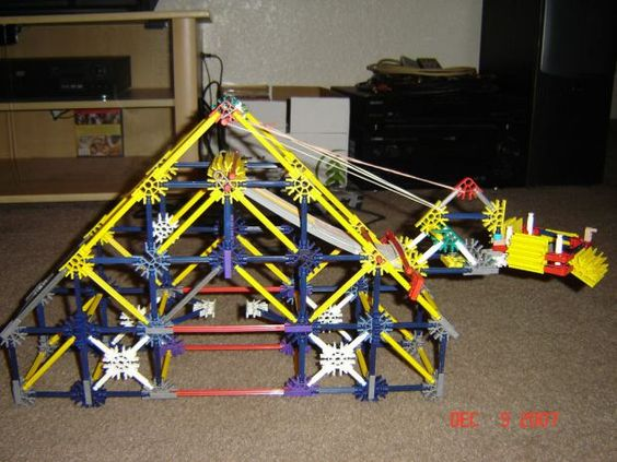 Darbysboy1 constructed his trebuchet using K'NEX pieces with 81 rods, 52 connectors and eschews counter weights in favor of rubber band tension. Unfortunately, this is the last surviving picture of his original as he tried using more rubber bands to increase the throw distance, which wound up destroying the trebuchet outright. Best to stick to counter weights. (Link)