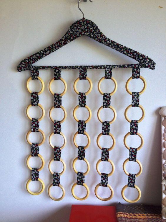 Cabide de madeira revestido com tecido (verificar cores disponíveis) com 25 argolas de madeira.  Muito útil para organizar lenços, cintos, colares, óculos ou o que sua necessidade pedir!!