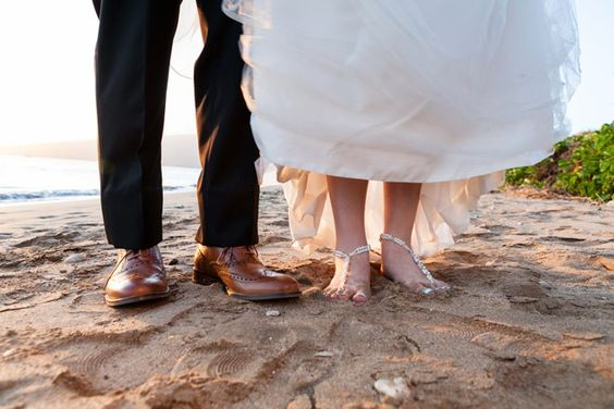 Groom wore brown dress shoes and bride wore foot jewelry