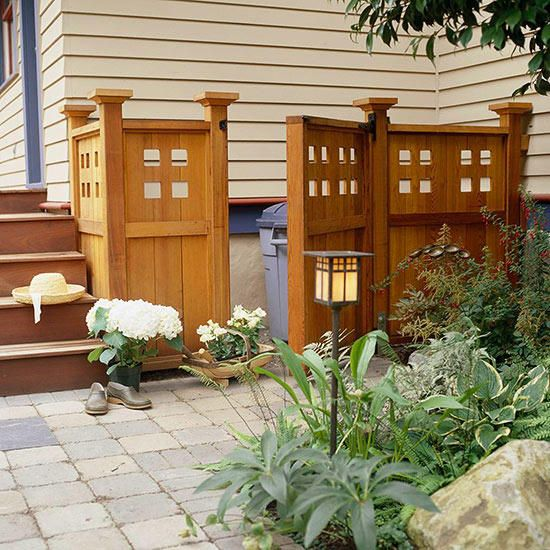Nothing ruins the view in a small backyard faster than a set of garbage cans blown over in the wind. Instead of having your garbage in plain sight, build a wooden surround to keep them contained. Here, a set of stylish wooden panels camouflages the homeowners garbage with a little space left over for bags of potting soil and extra garden tools. When the gate panel is closed, everything is completely hidden.