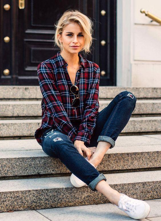 Jeans com barra dobrada, camisa xadrez e tênis.