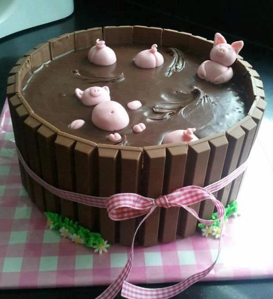 Happy as a Pig in Mud Cake! Fondant icing for the pigs, any kind of cake in 2-9 in round cake pans, icing around cake to hold KitKats in place. Top the cake with melted chocolate icing then place your fondant pigs in the melted icing.
