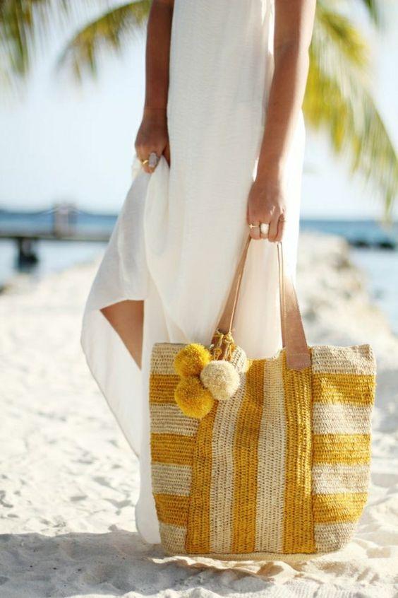 une robe longue de plage blanche, un sac en paille beige, jaune