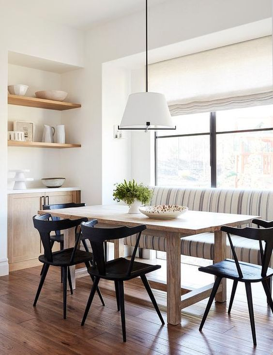 Light wood dining table surrounded by sleek black chairs under a white drum hanging light. A striped upholstered dining bench features gray and blue fabric against a dining room window fitted with a linen roman shade. Amanda Teal Design