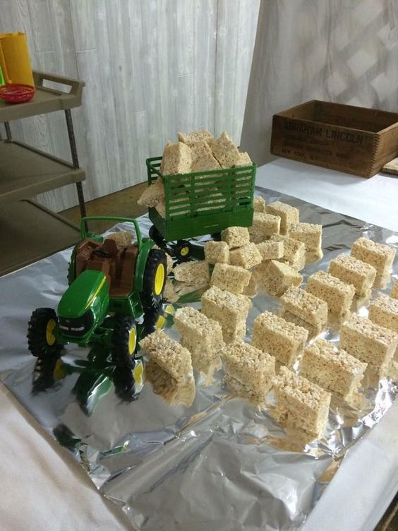 """Cute idea for a kid's farm themed birthday party: tractor prop with Rice Crispy Treat """"hay bales""""."""