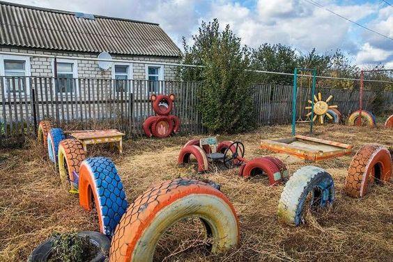 aire de jeux enfant - déco en pneus de voitures multicolores, voiture de course et bac à sable