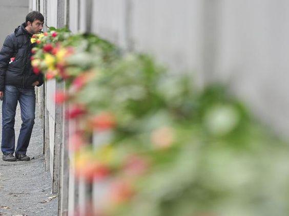 Flores colocadas no muro homenageiam as vítimas no 21º aniversário da queda do Muro de Berlim, em 2010  Foto: AFP