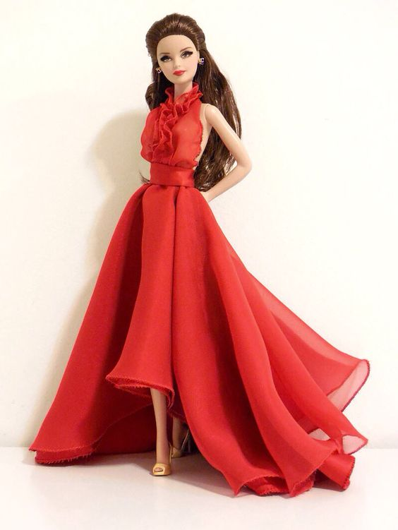 Barbie in custom red silk & chiffon halter gown w/pockets & ruffle bodice detail. Accessorized w/sapphire earrings & gold pumps.: