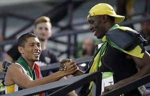 Usain Bolt shakes hands with 400m winner Wayde Van Niekerk.