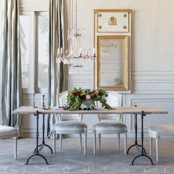 Romantic #FrenchCountry dining room with rustic dining table with delicate iron legs, crystal chandelier, antique replica dining chairs, and French trumeau mirror. #NordicFrench #elegantdecor