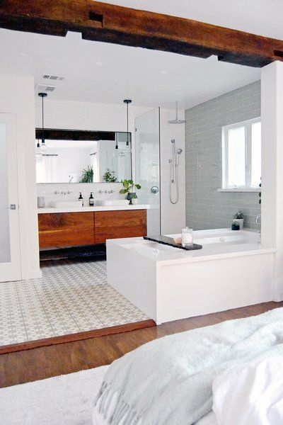 A soaker tub and large reclaimed beam (salvaged from an old barn) creates a casual boundary between bath and bedroom. Moroccan-inspired cement tile, a custom vanity, white quartz Kohler bath fixtures create a spa-like feel. Photo 3 of 9 in Spenla Master Bed & Bath Open Space Concept