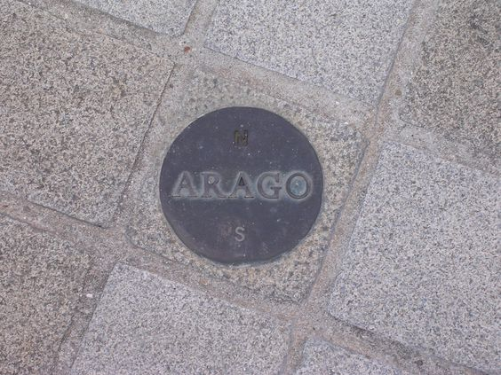 """Arago medallion near the Louvre pyramid. In his  """"Hommage à Arago,"""" commissioned as a memorial to François Arago (1786-1853), Jan Dibbets set over a hundred of these bronze medallions into the ground along the Paris Meridian from the southern to the northern boundaries of the City. Each of them is 12 cm in diameter, with Arago's name and showing north and south.  (Photo credit: Poulpy) Mona Evans, """"Full Meridian of Glory - book review"""" http://www.bellaonline.com/articles/art181703.asp"""