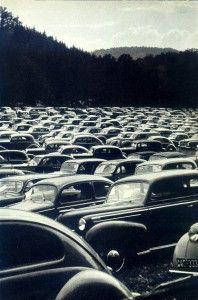 und ein Parkplatz mit einsamen Autos vor deutschem Wald ▼