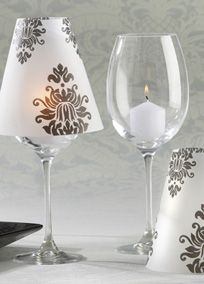 "Introducing a new standard in elegant table decor! Imagine the mesmerizing glow our exquisite black-and-white Damask Vellum Shades will create throughout your reception hall.  Unforgettable doesn't even begin to describe it!  Features and facts:   Classic black-and-white damask pattern adorns a translucent, vellum shade.  Shade fits on standard wine glasses to create a softly glowing table lamp.  Assembled shade measures approximately 4 3/4"" h x 4 1/2"" in diameter.   Wine glasses and candles…"