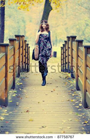 Beautiful hippie girl fashionalby posing on a wooden bridge in autumn scenery wearing maxi long dress and gorgeous make up. by cellistka, via ShutterStock