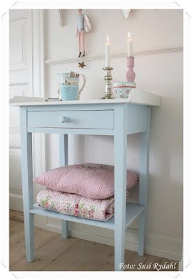 Little blue bedside table used for blanket storage in the guest room.