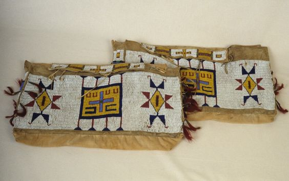 Saddle Bag, Sioux. 19th/20th c.  x 20 1/2 in. ( x 52 cm).  Riding Equipment.  Beads on Leather.  Gift of Mrs. Edward H. Angle.  Flat rectangular bag made of hide and cloth. Solidly beaded with complex geometric designs in yellow, red and blue on white. Metal clamps and red tassels on the sides. Pomona College Museum of Art.