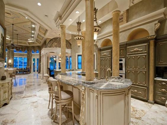A stone-topped island surrounded by dramatic columns serves as the focal point of this ultra-lavish gourmet kitchen.  WOW