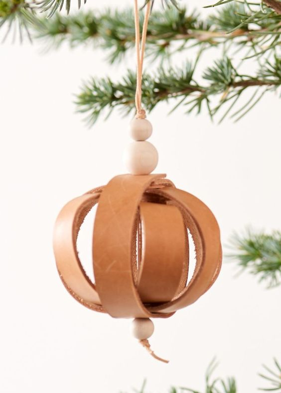 Handmade christmas ornament made as a xmas bell in nature leather and wooden beads. Hight: 9 cm (without suspension), 16 cm (with suspension)