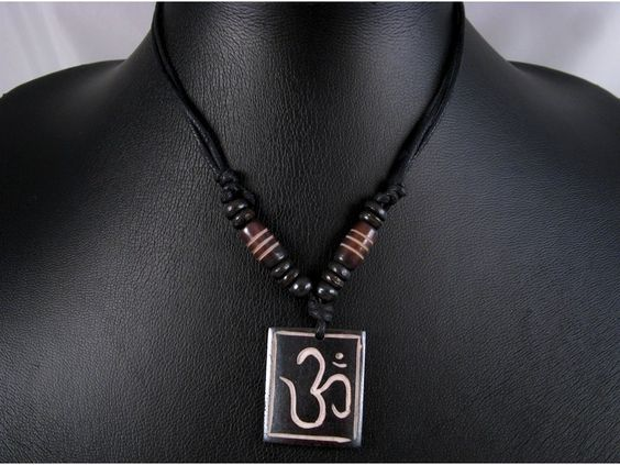 Beau collier composé d'un galon noir et d'un pendentif en os de buffle, avec le symbole Om. ------------------------------------------------- Necklace made from buffalo bone with the symbol Om.