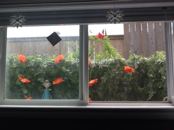 My daughter in law came up with this idea to camouflage my ugly window wells with artificial vines and flowers ... Love the difference!