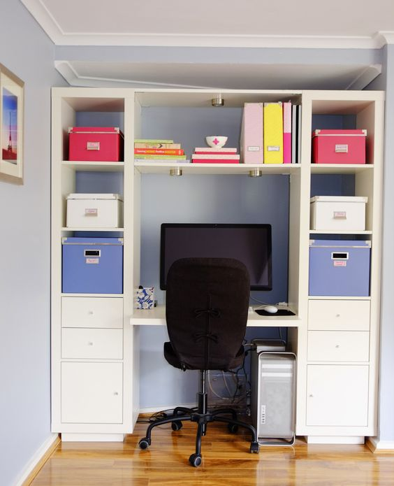 An organised home office space using storage boxes to organise important…