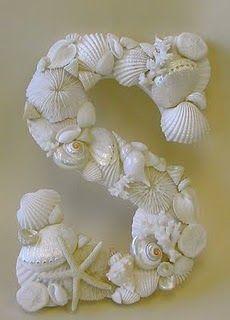 Seashells on wooden alphabetic letter