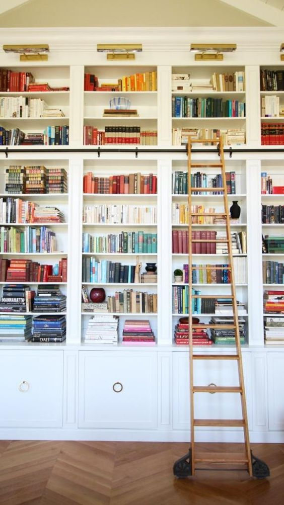 library with painted built-in shelves, brass picture lights, herringbone floor