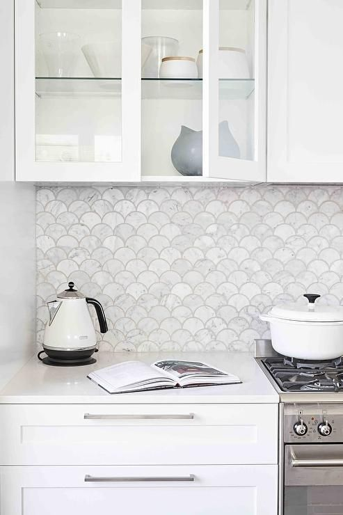 Gorgeous white kitchen boasts carrera marble fan shaped backsplash tiles positioned above white shaker cabinets with long nickel pulls and beneath glass front upper cabinets fixed beside a concealed vent hood mounted above a stainless steel oven range.: