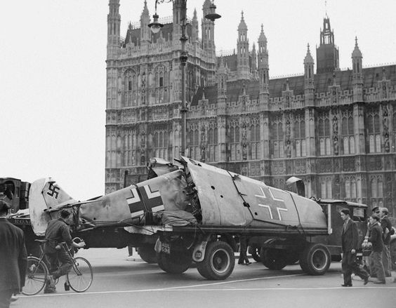 A crashed Messerschmitt Bf-109 is towed past the Houses of Parliament in London during World War II.