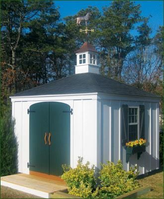 "10' x 10' Race Point - Race Point hip roof design shown features 5' arched double bead board doors with custom oak door handles. One 24"" x 41"" opening window with z brace shutters and window box. Standard siding stained white. Standard trim package painted white. Upgraded hardware, Walpole Woodworkers 20"" Ipswich cupola holds customers' weathervane."