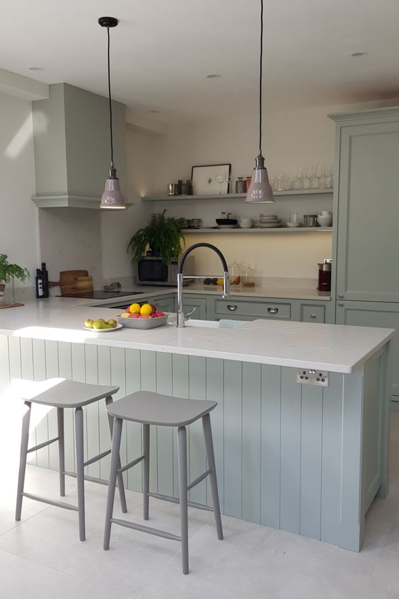 This stunning, pale green hand painted kitchen has a large breakfast bar with built-in sink and lovely open plan shelving creating a country feel. The beaded cabinets are complemented with white quartz worktops and chrome fixings #lightgreenkitchen #traditionalkitchen