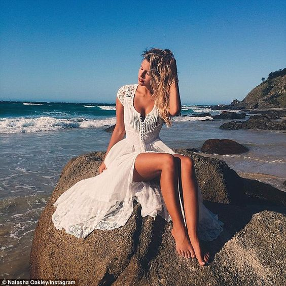Life is a never-ending photo shoot! Swapping her bikini for a lace frock, Natasha cut a decidedly more bohemian figure as she posed for another photo, perched on the edge of a beach-side ledge